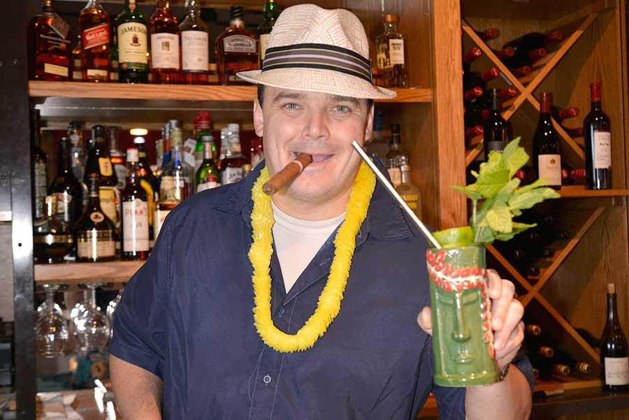 a man with a hat holding a green drink